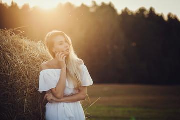 Gentle portrait blonde girl in a field on sunset