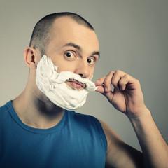 Funny portrait of trendy man making moustache and beard of shavi
