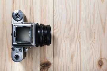 Old medium format camera on natural wooden table