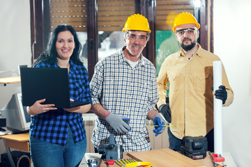 Construction worker and couple looking at the laptop