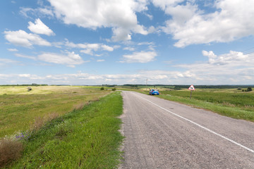 Highway, green meadow, car and road sign, blue sky with clouds