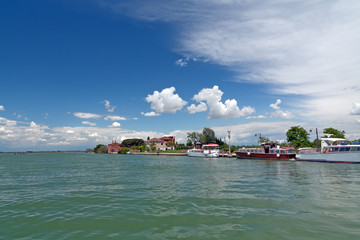 Sea, green island, old buildings, staying vessels, sunny weather