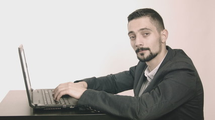 Business man programmer typing at his desk and looking at camera