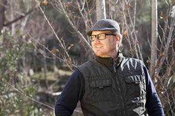 Hombre pelirrojo con gafas y gorra en el bosque