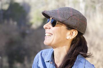Mujer con gorra y gafas de sol sonriendo