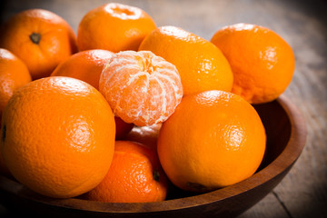 tangerines in dish on wooden table