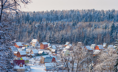 Winter landscape with views of the village in a forest