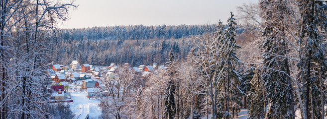 Winter panoramic landscape with views of the village in a forest