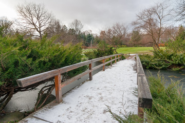 Landscape with first snow on a wooden bridge in Japanese garden