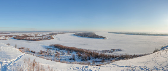 Winter panoramic landscape with frozen river from the high bank