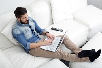 man typing on sofa