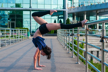 Girl stands on the hands, upside down. Acrobatics, ballet, dance