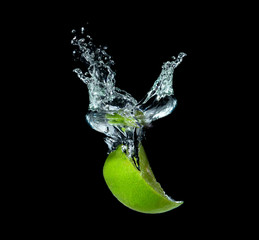 lime slices falling into water on black