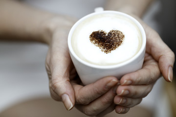 The girl holds a cup of coffee with heart from cinnamon
