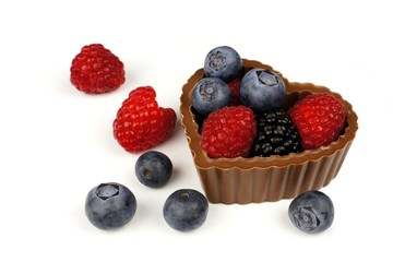 Heart shaped chocolate cup filled with fresh berries over white