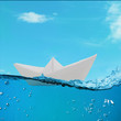 paper boat floating among the waves in the ocean