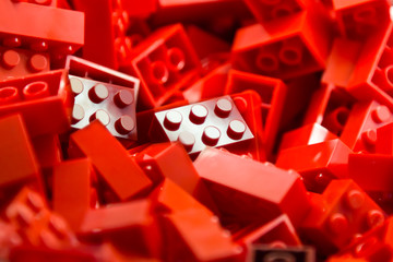 Pile of red building blocks with highlight on one piece.