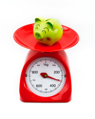 The smile green piggy bank on the scales white background