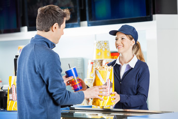 Seller Giving Popcorn And Drink To Man At Concession Stand
