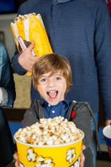 Portrait Of Excited Boy Showing Popcorn At Cinema