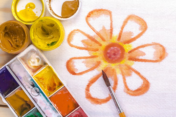 artist's brush on a background painted orange flower