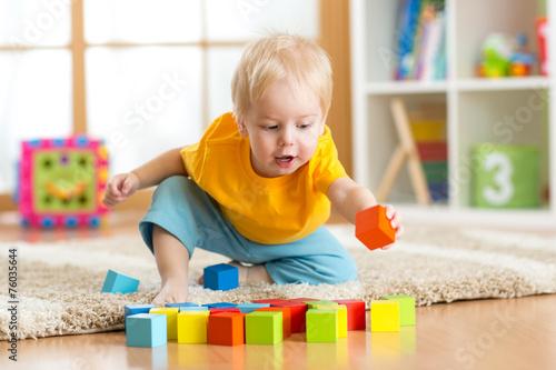 Leinwanddruck Bild child toddler playing wooden toys at home