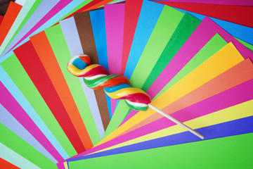 Colorful twisted sweet lollipop with brightly colored papers