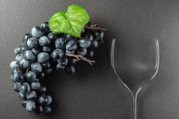 Wine glass made of forks and grape on black