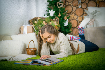 girl reading a book lying on the carpet