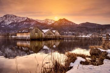 Gebirgssee mit Bootshäusern und Steg