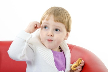 little blond girl sitting on a couch and holding a a bagel