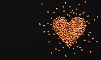 Heart-shaped arrangement of premium buckwheat groats on black