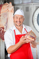 Happy Butcher Holding Meat In Shop