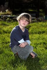 Young boy in garden looking over his shoulder