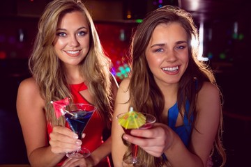 Pretty friends drinking cocktails together