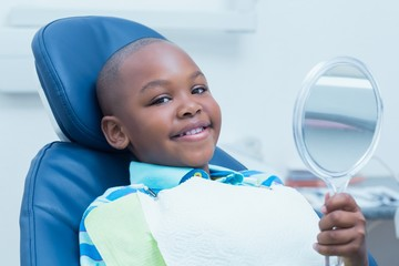 Boy holding at mirror in the dentists chair