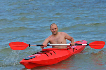 Young caucasian man kayaking in Black Sea
