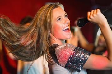 Happy blonde singing karaoke into mic