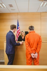 Lawyer and judge speaking next to the criminal in jumpsuit