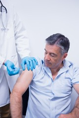 Doctor giving injection to his patient
