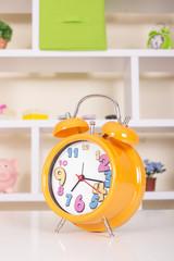 Orange alarm clock on table