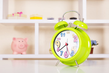 Green alarm clock on table with shelf on background