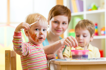 mother and little boys messily playing with paints