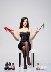 Young and attractive woman choosing shoes over grey background