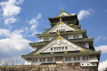 Osaka Castle in Japan during cherry blossom season in spring.