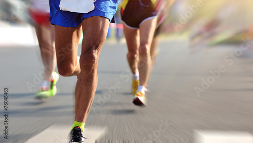 marathon athletes legs running on city road - 76048463