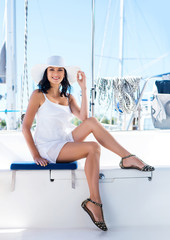 Young brunette woman in a white dress relaxing on a boat