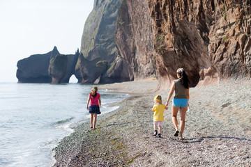 Mother and her daughters walking at the sea