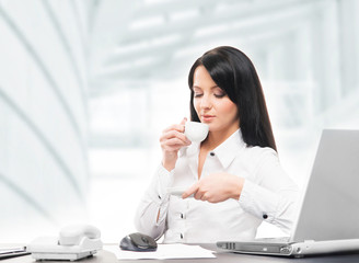 Young and attractive business woman drinking morning coffee in o