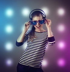 Young woman in heart shaped eyeglasses and earphones having fun